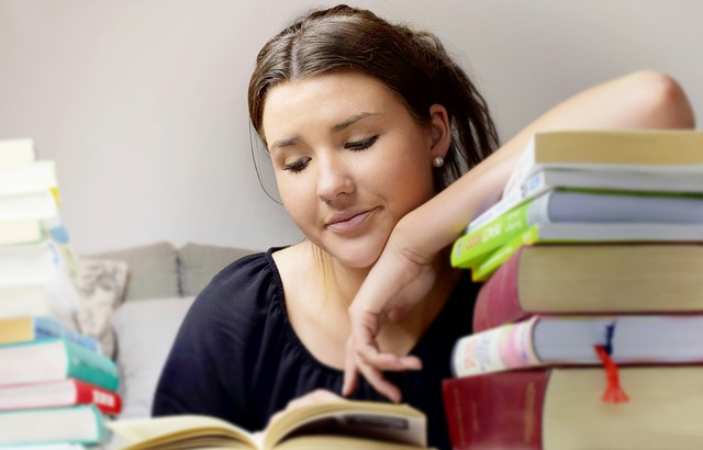 Teenage Girl studying for exam - looking at text books with worried face