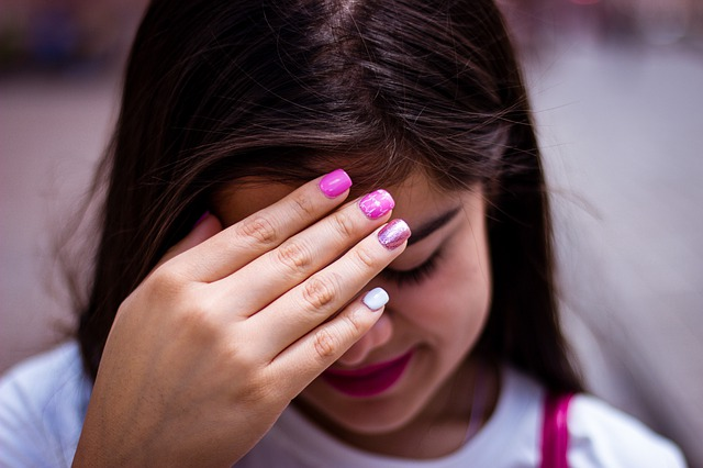 Teenager Girl looking down with hand over face - shy