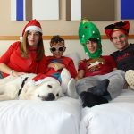 Family relaxing wearing Christmas hats
