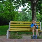 boy looking lonely on bench