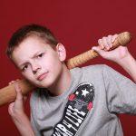 boy staring into camera with baseball bat behind his head