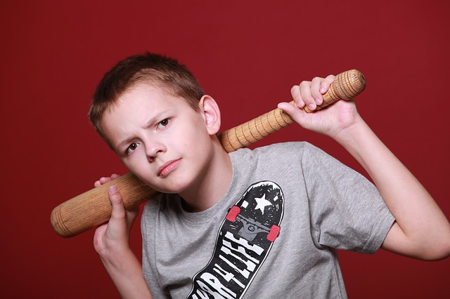 boy staring into camera with baseball bat behind his head