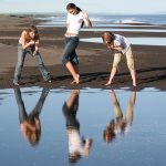 3 girls at beach - posing and looking at reflection in water