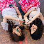 two girls lying on ground making heart shapes with their hands