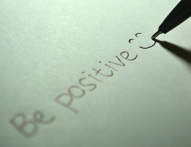 "a pen writing the words ""be positive"""