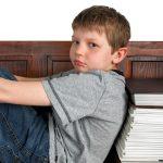 Sad boy sitting with back to books