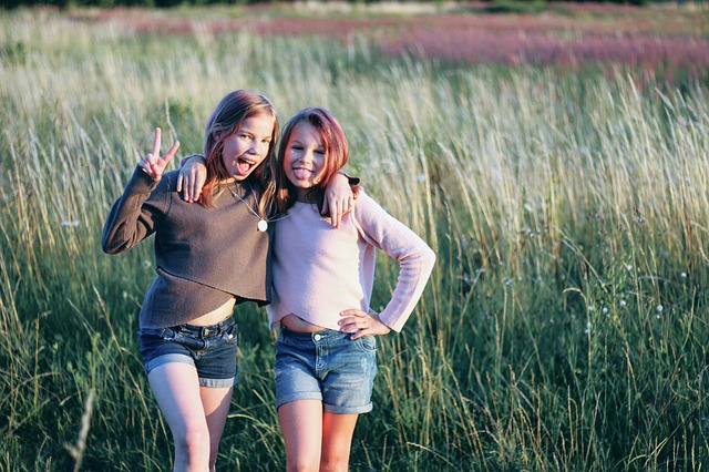 2 teenage girls smiling to camera with arms round each other