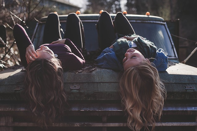 Two girls laying over car bonnet. Talking and smiling.