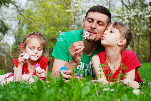 Dad with 2 daughters lying on grass blowing bubbles