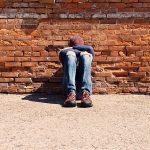Teen boy sitting on floor with head in hands