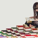 Girl sitting reading on a floor full of books