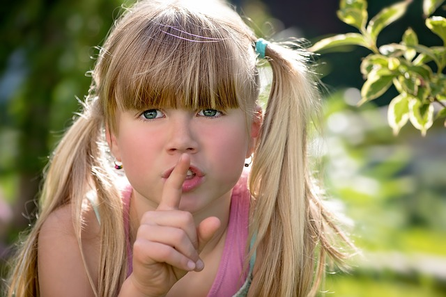 Girl with finger up to lip- Shhhh