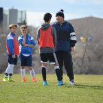 Boy talking to football coach. 2 other boys looking nervous in background.