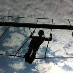 Boy climbing on high rope obstacle