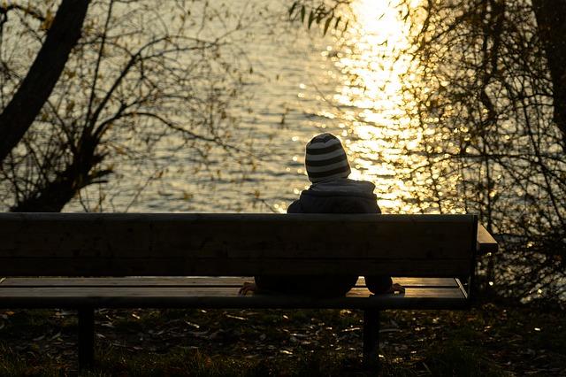 Boy Sitting Alone by Water