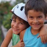 2 boys hugging - one with motorcycle helmet on