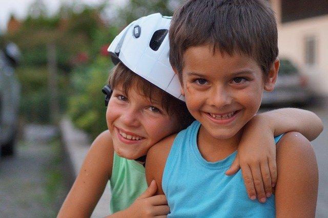 2 boys hugging - one with motorcycle helmet on