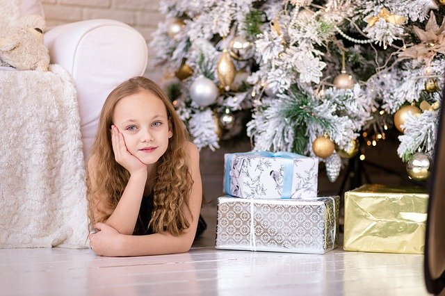 Girl under Christmas Tree with Gifts