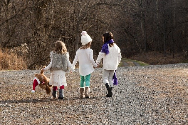 3 Sisters holding hands walking outside
