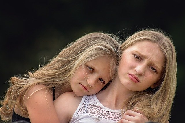 One girl cuddling another girls who looks uncomfortable