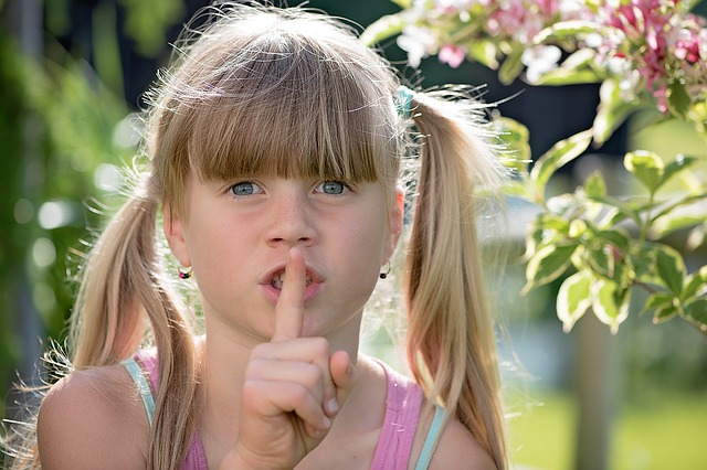 Girl with finger over mouth - stop talking