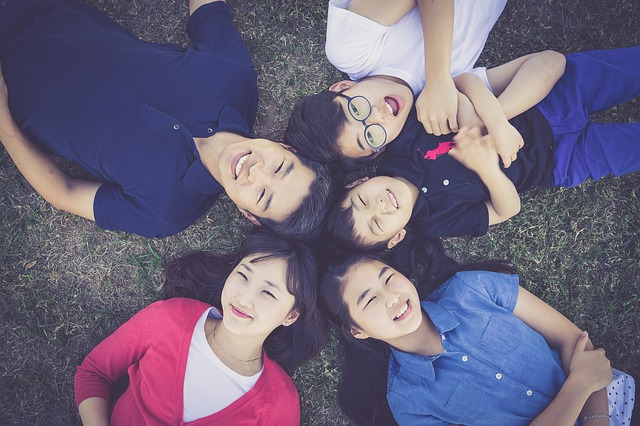 Family lying on grass looking up at camera