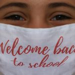 Girl with Face Mask on that says 'Welcome Back to School'