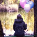 woman sitting alone on bench with a bunch of ballooons