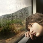 Little boy looking bored - staring out of window - raining outside