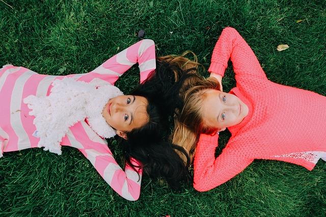 Girls lying head to head on grass