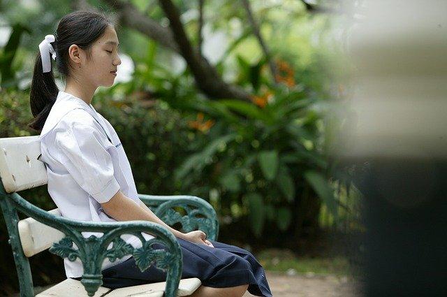 Girl Sitting on Bench in Sunshine Meditating