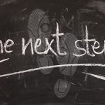 Chalk board with words the next step written in white chalk
