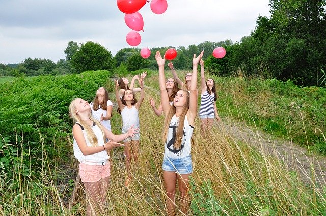 Group of teenage girls letting off balloons in a field