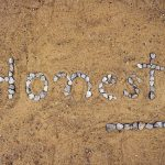 The word honesty written in pebbles in sand