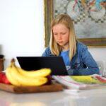 Girl doing oneline school at dinner table