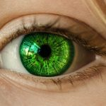 Close up shot of girls green eyes - virus cells reflected in her eye