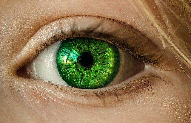 Close up shot of girls green eyes - virus cells reflected in her eye