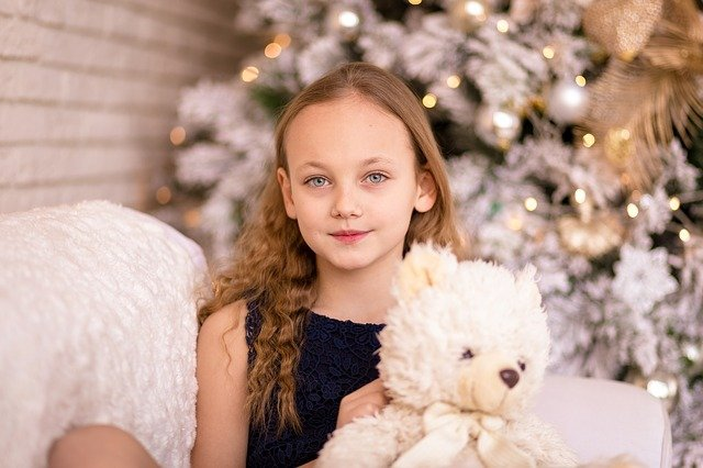 young girl holding teddy bear in front of christmas tree