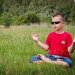 Young boy sitting cross-legged on grass meditating
