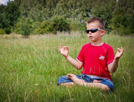 Young boy sitting cross-legged on grass meditating