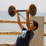 Boy Lifting Weights by Ocean