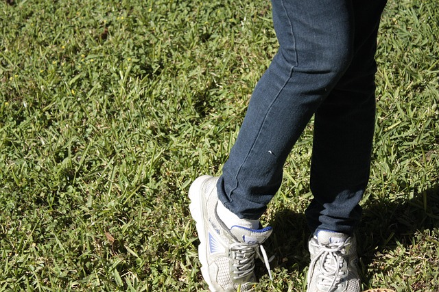Girls legs in jeans and trainers - one leg turned in shyly