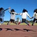 4 girls holding hands and jumping into the air