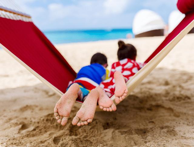 two kids lying in a hammock on the beach