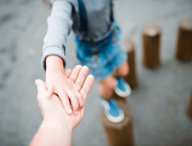 parent and child hands playing together in park