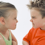boy and girl pulling angry faces at each other