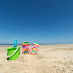 bucket and spade and kids flip flops on the beach