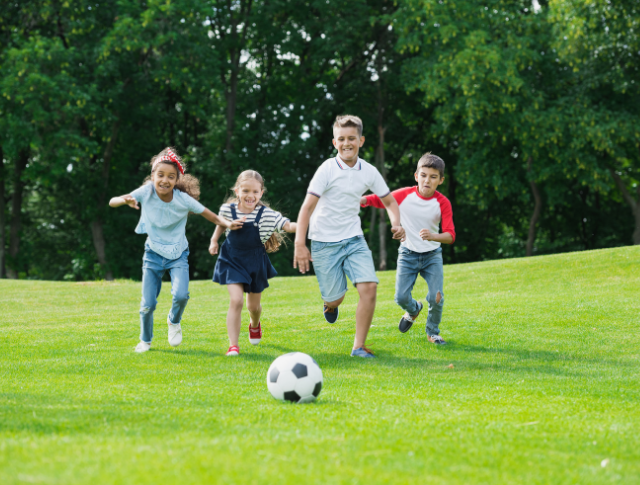 groups of kids of mixed ages playing football in the park