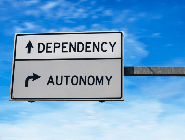 road sign with arrows pointing to dependency and autonomy
