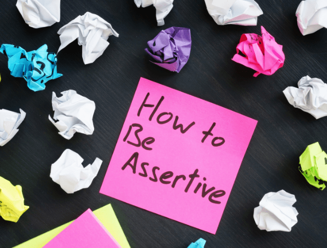 Post it note with How to Be Assertive written on it
